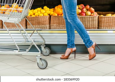 Legs of the female customer with cart against the shelves of fruits in the shop
