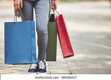 Legs of female shopaholic with many paper-bags