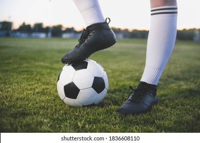 Legs of a female soccer or football player on ball at stadium, close up