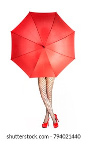 legs in fishnet stockings and shiny red high heels shoes behind an open red umbrella.