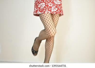 Legs of fishnet in tropical mini dress