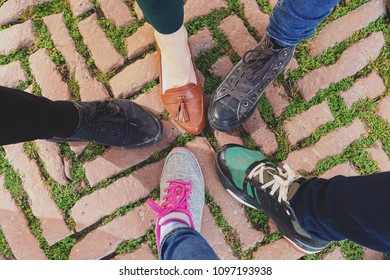 Legs of five friends in different shoes standing together, top view