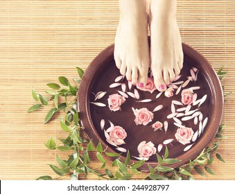 Legs, flowers, petals and ceramic bowl. Spa, recreation and skin care concept.