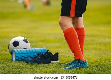 Legs of a football player boy in boots cleats with a ball and foam roller on the green lawn of the stadium. Football equipment closeup