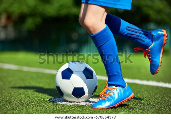 Beine eines Fußballspielerjungen in Stiefeln mit Stockfoto