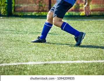 Legs of football player in motion on the field. Soccer player legs in action