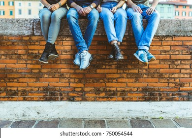 Legs of four teenagers sitting on a bricks wall. Close up view on bottom part of the body, two girls and two boys sitting together in the city. Friendship and lifestyle concepts