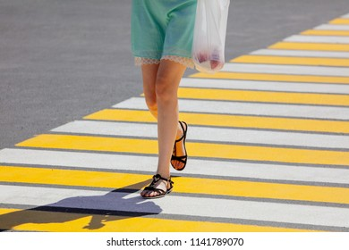 Legs of a girl crossing the road through a zebra