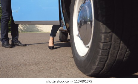 Legs of girl getting into retro auto. Man opens and holds door of vintage car for the beautiful woman in high heels shoes. Chauffeur opening door of old automobile for female passenger. Close up.