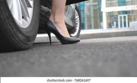 Legs of girl getting out of auto. Business man opens and holds the car door for the beautiful young woman in high heels shoes. Chauffeur opening door of automobile for female passenger. Close up.