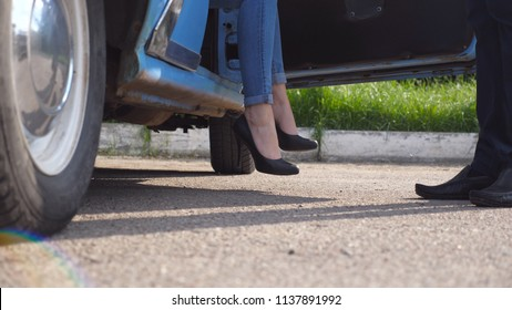 Legs of girl getting out of old auto. Man opens and holds door of retro car for young woman in high heels shoes. Chauffeur opening door of vintage automobile for female passenger. Close up Slow motion