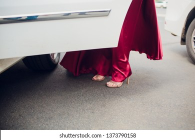 Legs of girl getting out of old auto. young woman in high heels shoes. Chauffeur opening door of vintage automobile for female passenger.