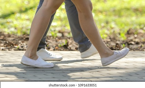The legs of a girl and a guy are walking along the road