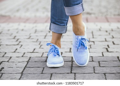 legs of a girl in jeans and blue sneakers on a sidewalk tile, a young woman strolling in a summer park, a concept rest and everyday style