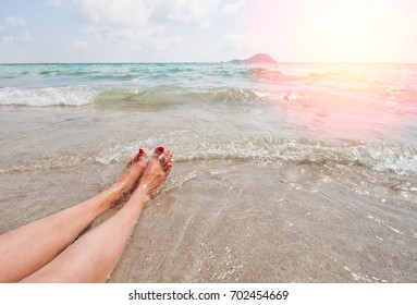 Legs of a girl on a sandy beach near the sea, a sea wave caresses the feet, a vacation pleasure relaxing a beautiful view