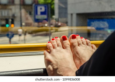 legs of a girl with a red pedicure on the window of a tourist bus