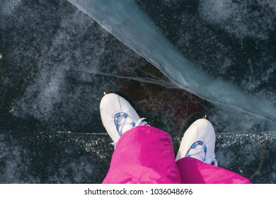 Legs of the girl in skates and pink winter warm pants on the beautiful ice of Lake Baikal with cracks and snow in winter on a sunny day.