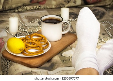 The legs of the girl in white socks are lying on the bed. Near there is a tray, tea in a large white metal mug, cookies, lemon. The background is blurred, there is a candle and beads