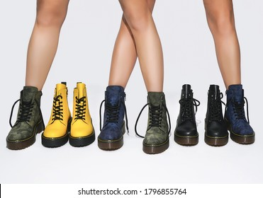 legs of girls in boots and fashionable new shoes at the presentation of the future collection shooting on a white background