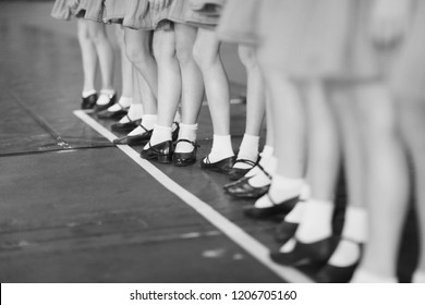 The legs of the girls dance group in the same shoes and white socks