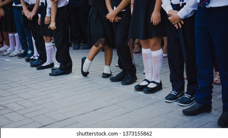 Legs of girls in white golf and boys in suit pants stand in line at the school track on September 1. September 1 - school line. First graders. Beginning of the school year.