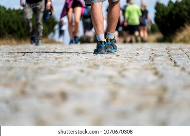 Legs going on the stone road. Hiking concept. Blurred effect, defocused background.