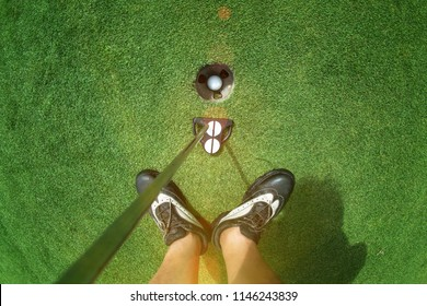 legs of golf player with putter standing on the green, putted a golf ball completed to the hole Successfully, cheerfully enjoy of the winner challenge