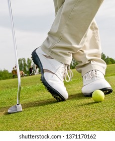 Legs of a golfer on green with ball and putter