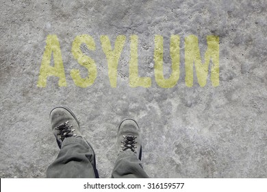 legs with gray boots and the word Asylum on the ground. Concept for Refugees on their way to Europe.