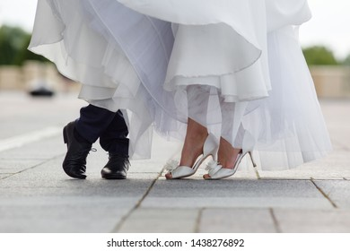 Legs of the groom in black shoes and brides in white heels with a snow-white hem of a wedding dress. Outdoor shot.