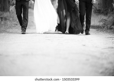 Legs of groom, bride and bridemaid and bestman. Black and white photo.