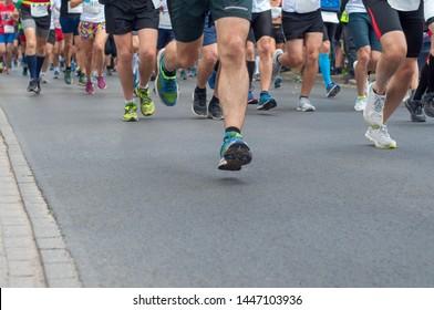 Legs group runners running on asphalt road. Selective focus.