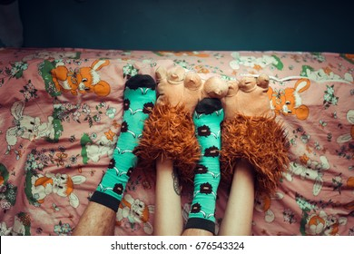 The legs of the guy in blue fun socks and the girl's legs into Slippers paws in bed