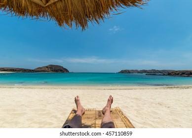 Legs of guy relaxing on beach under umbrella