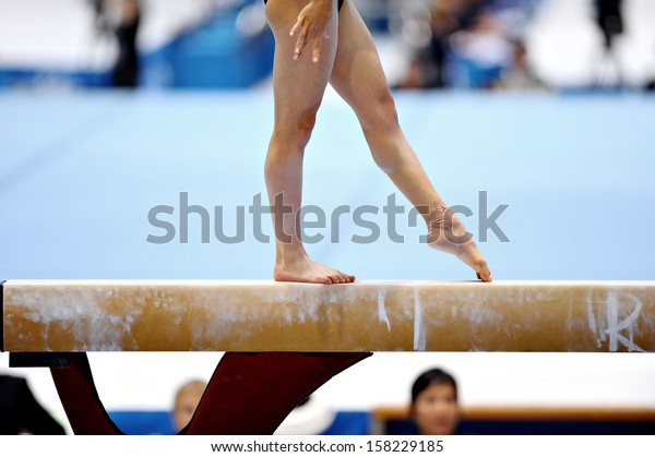 Legs of a gymnast are seen during an exercise on the balance beam apparatus