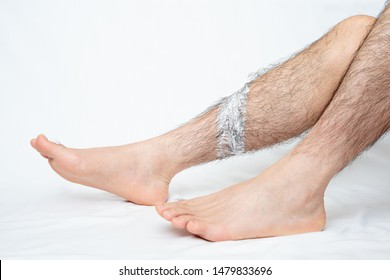 Legs hair removal for men. Apply hair removal cream to a part.