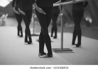 Legs and hands of gymnasts in choreographic positions in the rehearsal room during training