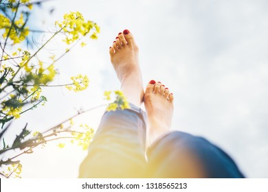 Legs up of happy female lying in deep yellow flowers meadow with bright sunny day optical sun beams flares. Happiness in nature concept POV image.
