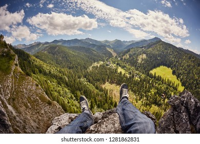Legs of a hiker sitting at the edge of the mountain.