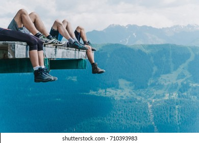 Legs of hikers of beautiful mountains view and green meadows, tourists legs in trekking shoes chilling on the air copy space