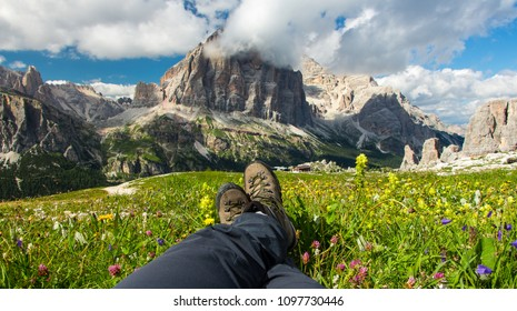Legs with hiking boots of hiker woman resting in the grass on a mountain top admiring Tofana di Rozes, Dolomites, Italy. Concept of freedom