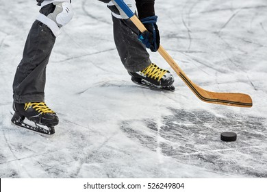 Legs of hockey player in skates, stick and puck on ice surface at outdoor skating rink.