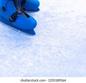 Legs of an ice skater in old vintage skates. Ice skratched background.