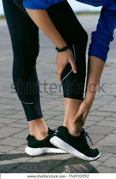 Legs Injury. Female Touching Painful Leg After Running Outdoors. Closeup Of Woman In Sneakers And Sportswear Touching Injured Leg, Feeling Pain In Ankle Joint After Sports Workout. High Resolution.