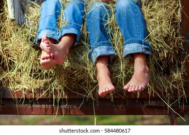 legs in jeans on a haystack
