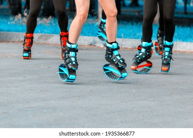 Legs in Kangoo Jumps close-up. A group of girls dancing in jumpers, in special sneakers on springs in the park on a sunny summer day.