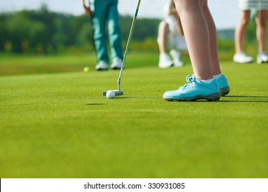 Legs of kids playing golf and hitting by putter on green