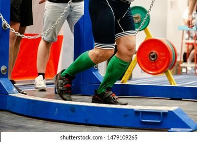 legs in knee-high-socks male powerlifter doing squat powerlifting