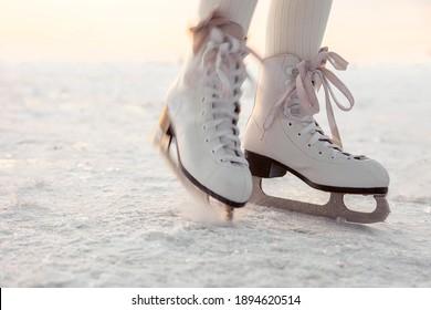 Piernas de niñita patinando sobre el hielo a la luz del atardecer. Deportes de invierno con fondo natural