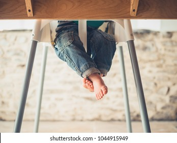 The legs of a little toddler sitting in a high chair at the dining table